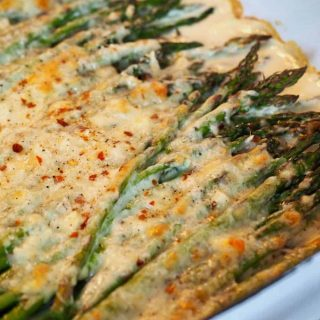 corner shot of cheesy baked asparagus with melted cheese in a casserole dish