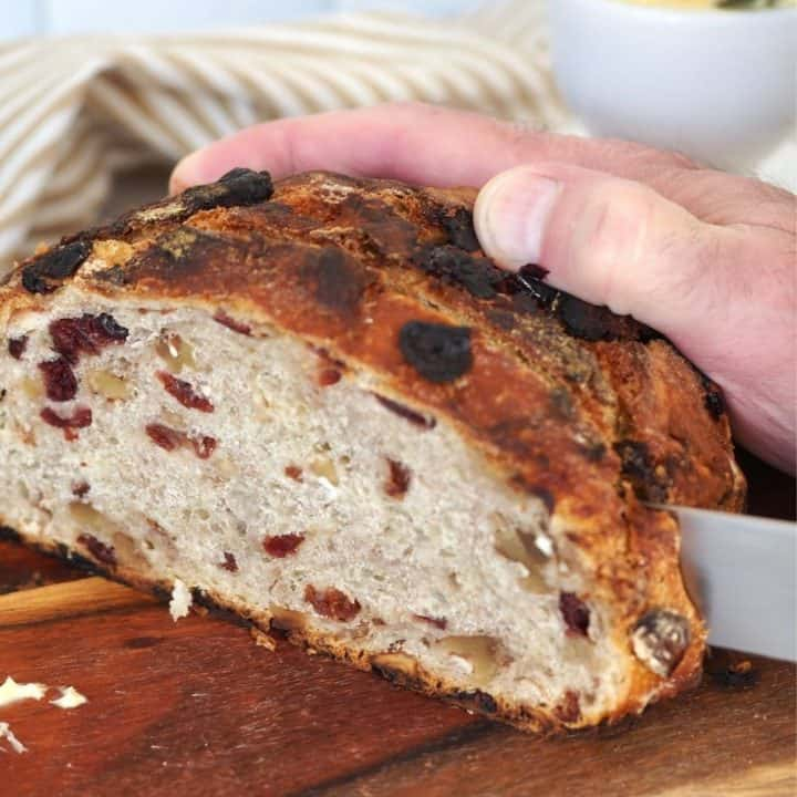 Man's hand holding loaf of bread, with serrated knife slicing a piece of the cranberry walnut loaf.