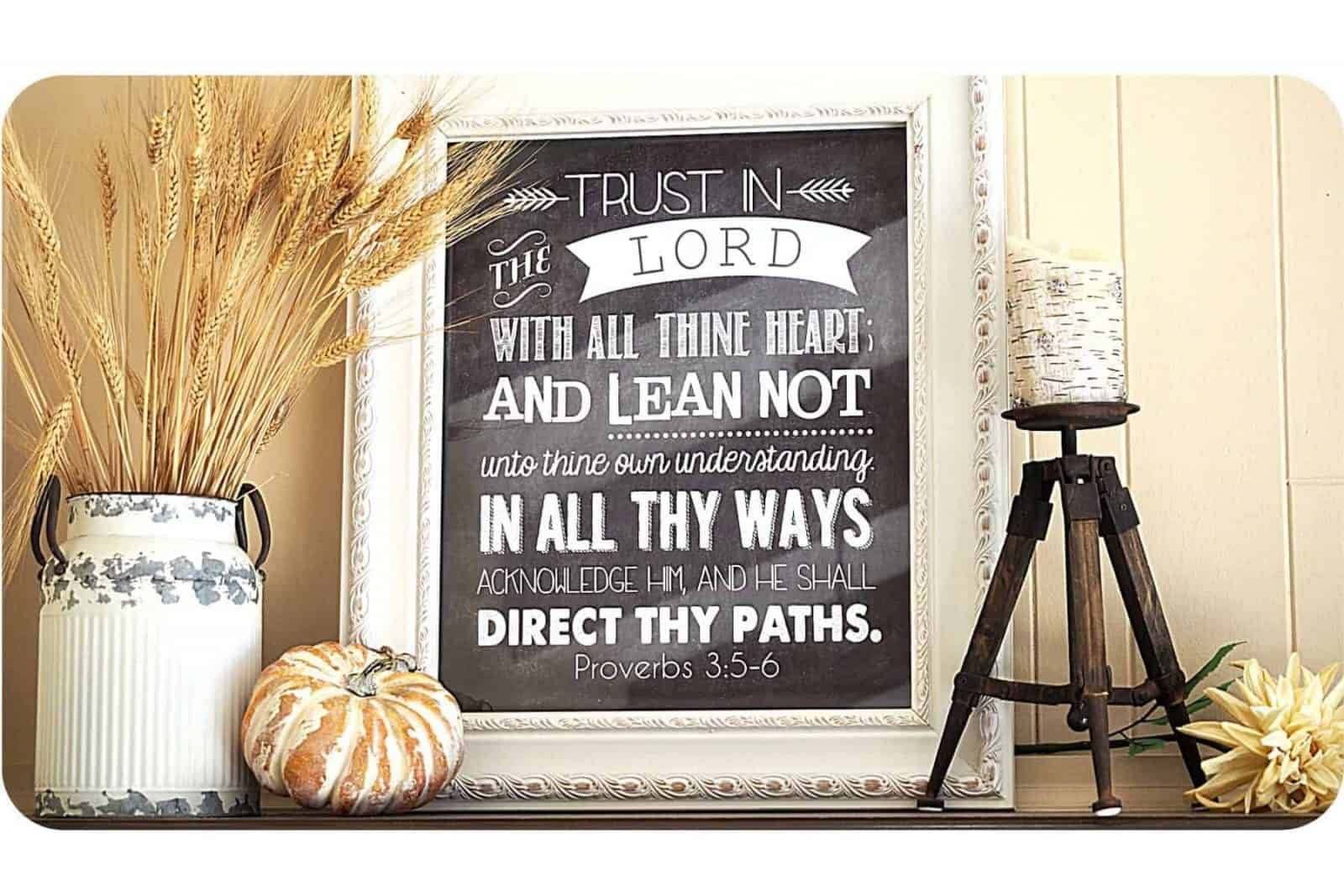Fall mantle, wheat in a bucket, with pumpkin, framed art with Proverbs 3:5-6 on it, candle on rustic stand with mum laying beside.