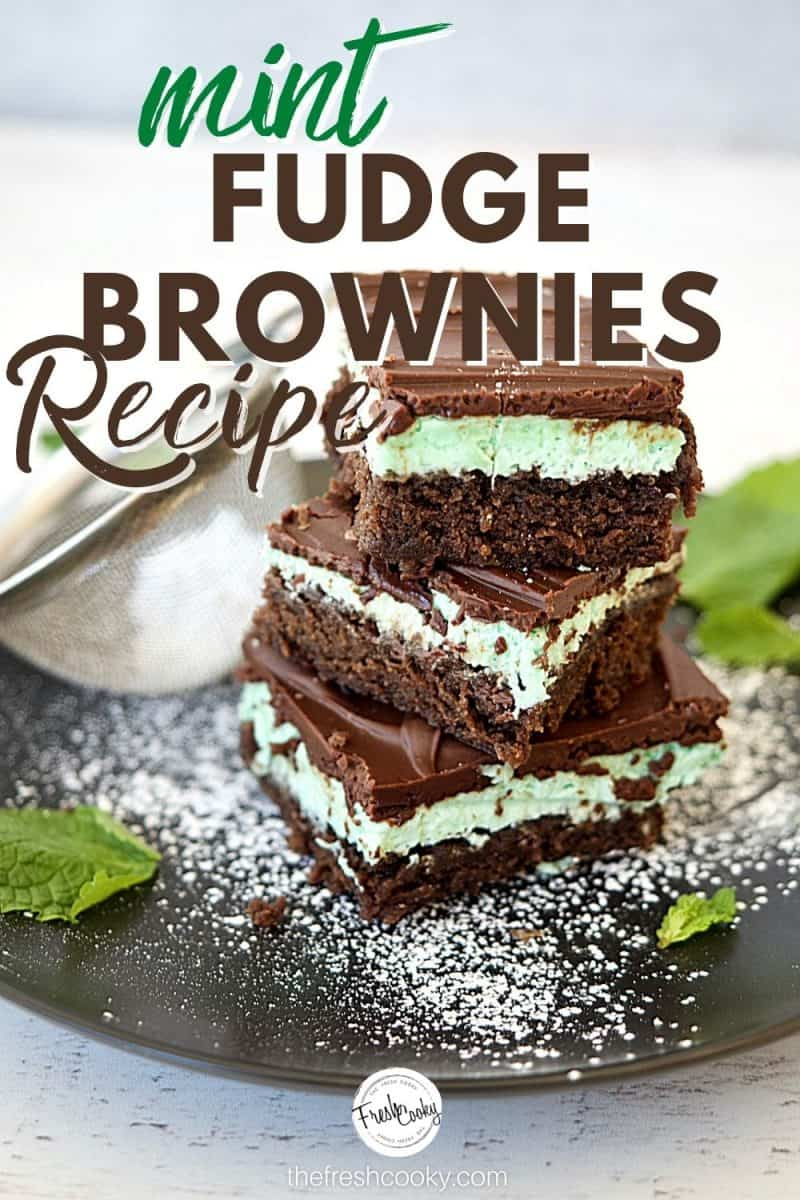 Pinterest Image for Mint Fudge Brownie recipe with three stacked fudge layered brownies on a black plate with powdered sugar sprinkled and mint leaves on plate