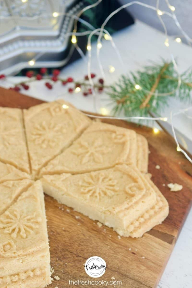 Molded Classic Shortbread Recipe using a snowflake mold, sitting on cutting board with twinkle lights and a sprig of evergreen