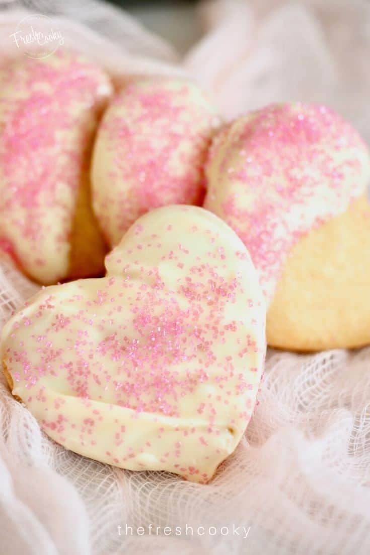 Heart Shaped Scottish Shortbread cookies dipped in white chocolate with light pink sprinkles.