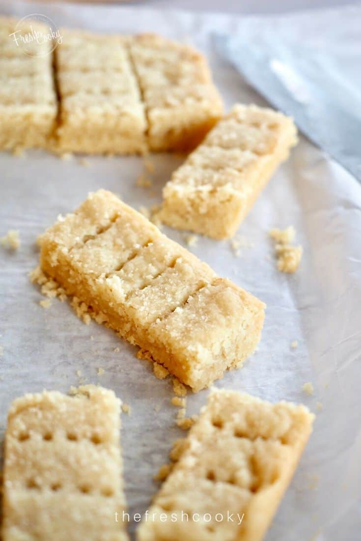 Classic Shortbread Recipe shows Shortbread fingers sliced and sitting askew on parchment paper