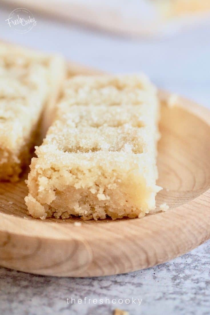 Close up shot of shortbread fingers on wooden platter with crumbs from Classic Shortbread Recipe