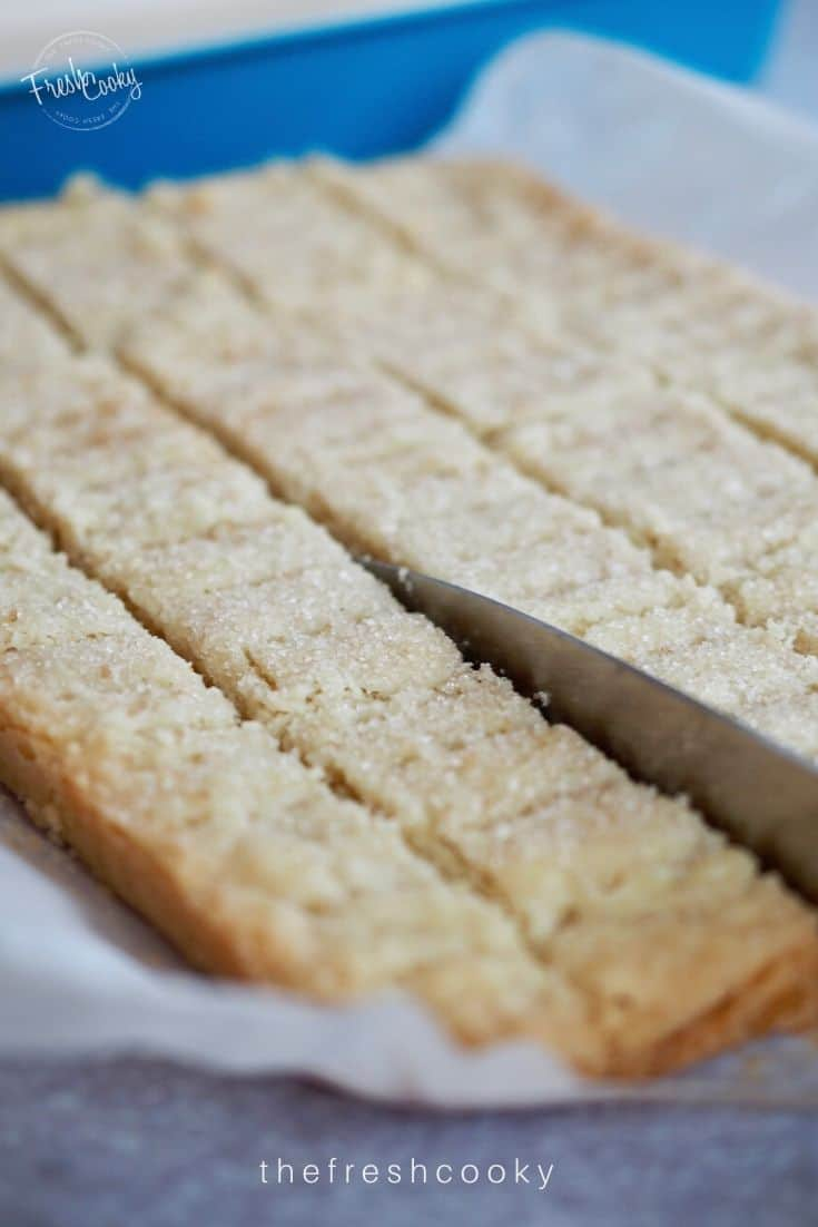 Best Classic Shortbread Recipe with image of knife slicing through the scored marks of fresh baked shortbread