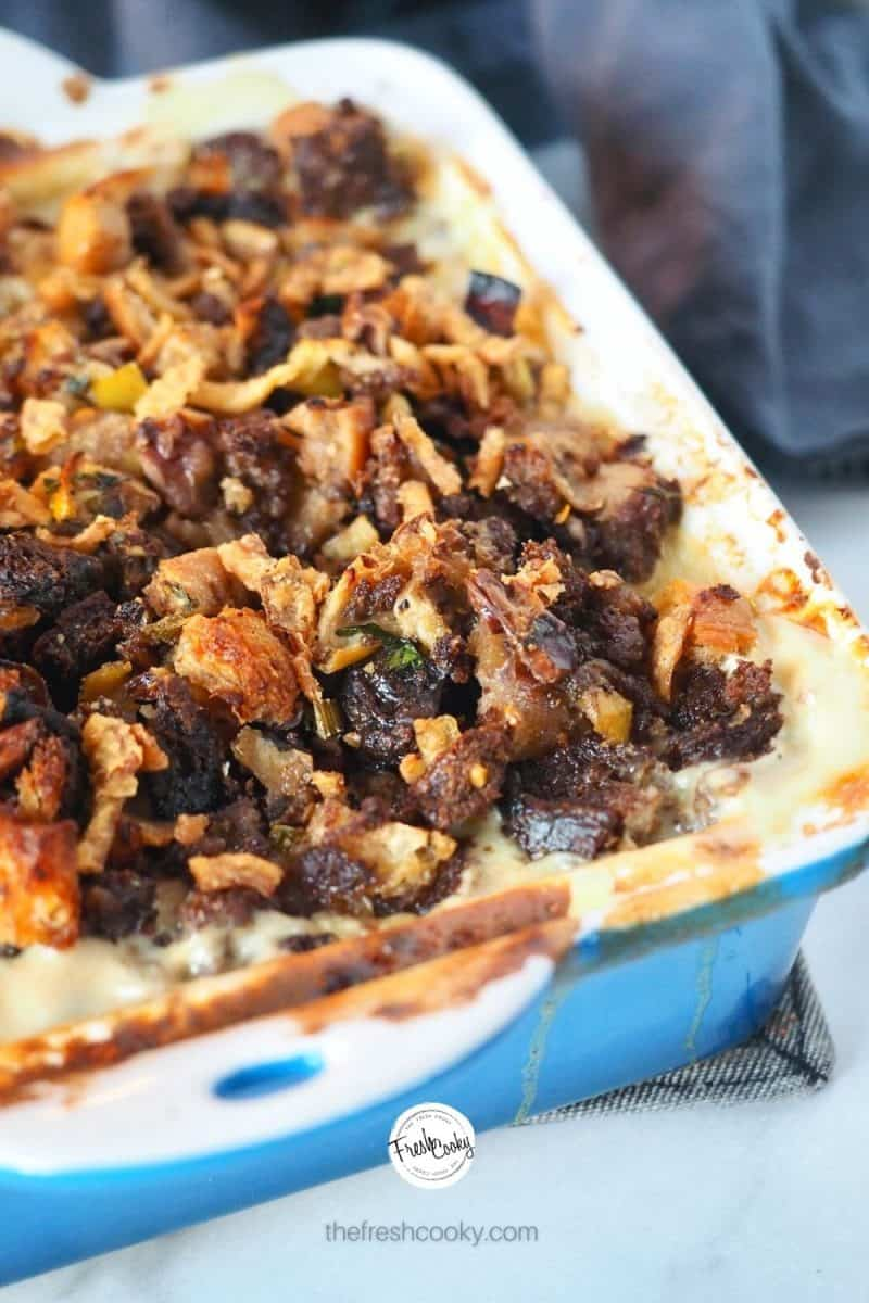 image of turkey divan in a blue square baking dish topped with leftover stuffing