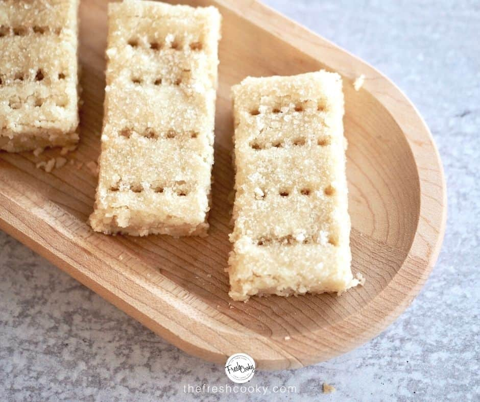 FB image of close-up of three fingers of shortbread on a wooden tray