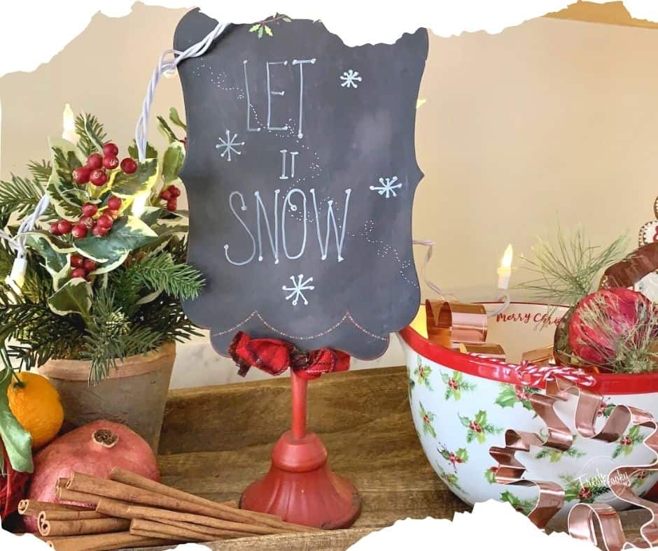"""Image of Christmas Kitchen decor vignette, small potted evergreen with orange, pomegranate and cinnamon sticks, next to a small chalkboard """"Let it Snow"""" sign, next to a Merry Christmas Batter Bowl filled with copper Christmas cookie cutters all sitting in a wooden bread board."""