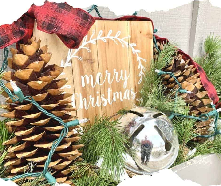 Outdoor Christmas decor with large sugar pine cone leaning against a wooden Merry Christmas sign with a big silver bell and fresh greens tucked around with a red and black checked bow and twinkle lights.