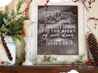 Image of Christmas decorated mantle, with words to O Holy Night, framed and tin of evergreens.
