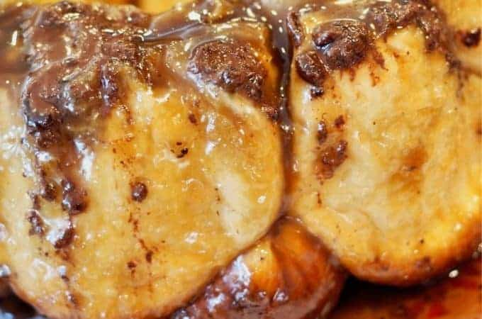Close up image of chocolate bourbon monkey bread oozing with caramel and chocolate on a red platter with a doily.