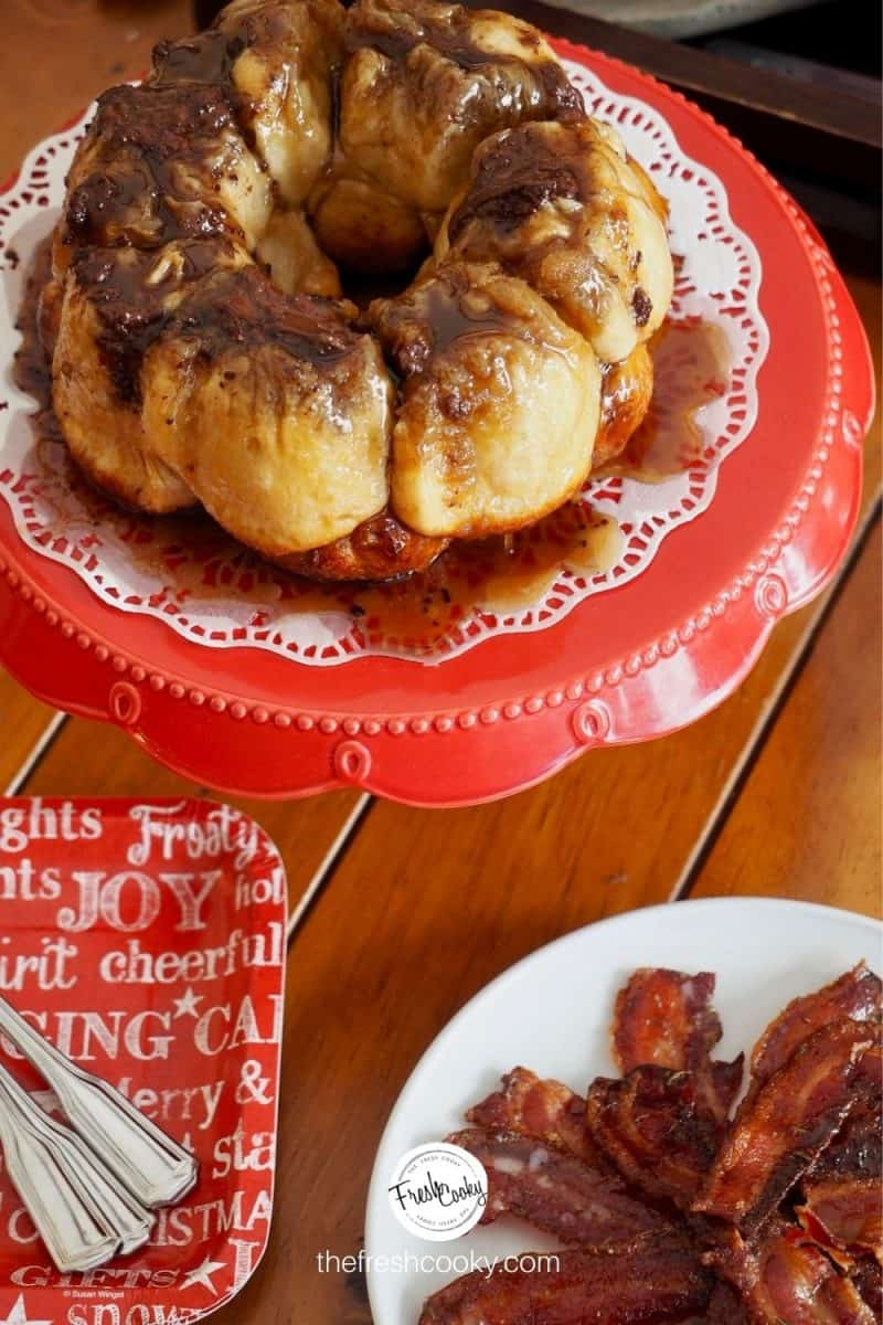 image of small chocolate monkey bread recipe on a red pedestal with a doily, sitting on a table with candied bacon and paper plates with forks nearby.