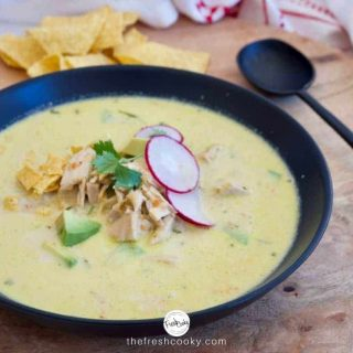 Facebook Image of black bowl of creamy chicken poblano soup garnished with avocado, radish slices, tortilla chips with a black spoon on the side and tortilla chips in the background.