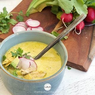 Facebook image for Creamy Chicken Poblano Soup in a rustic clay blue bowl with rustic soup spoon. with radishes on cutting board, fresh cilantro