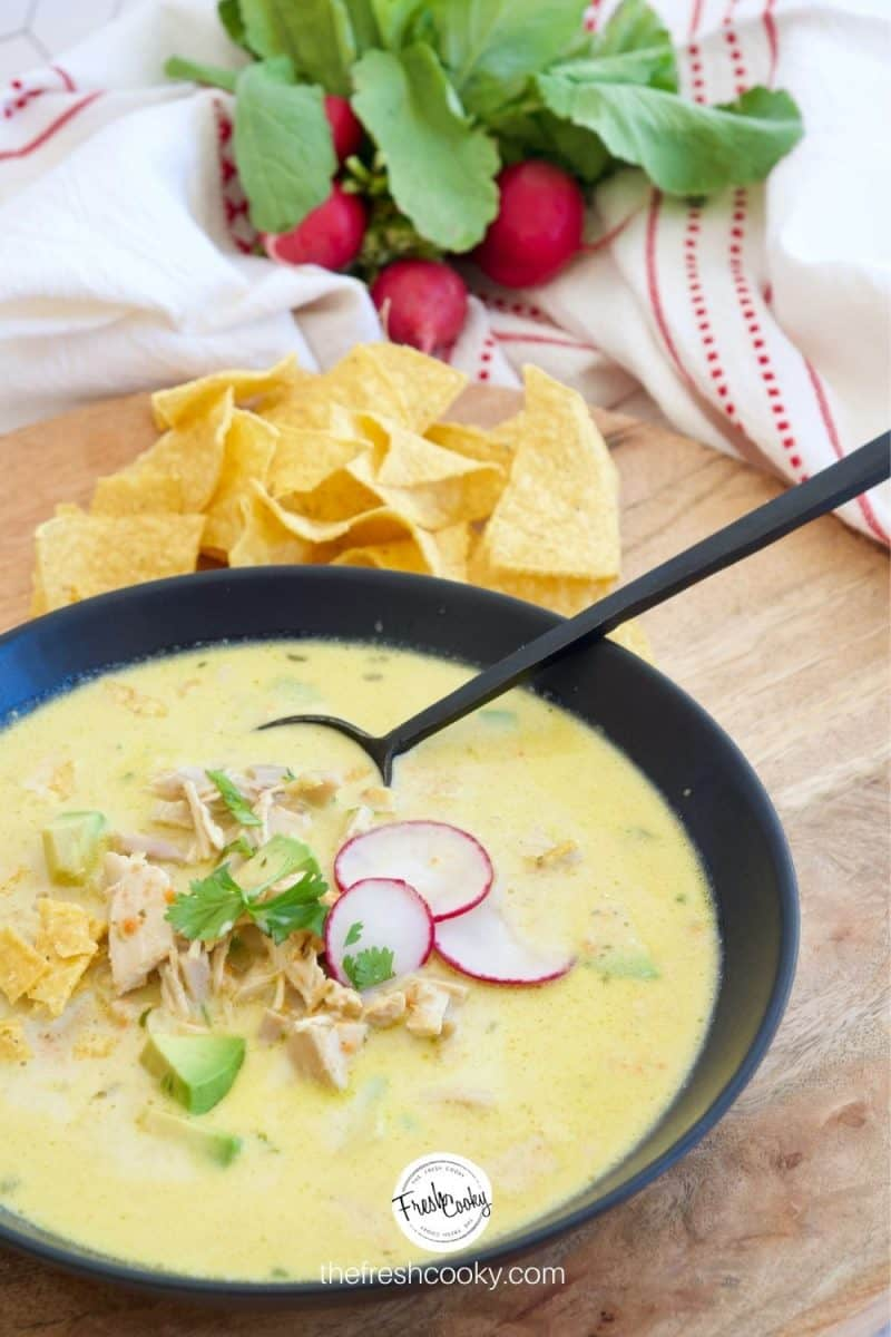 Creamy Chicken Poblano Soup in a black bowl with a black spoon on a wooden tray with tortilla chips and radishes in the background.