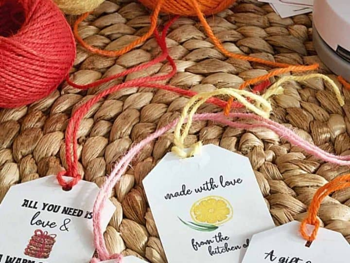 from the kitchen of gift tags on a rattan place mat with colorful spools of twine behind scissors.