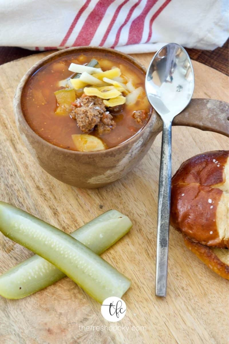 Wooden bowl with handle filled with healthy cheeseburger soup topped with farm cut cheesee, pretzels, dill pickle spears on a wooden tray