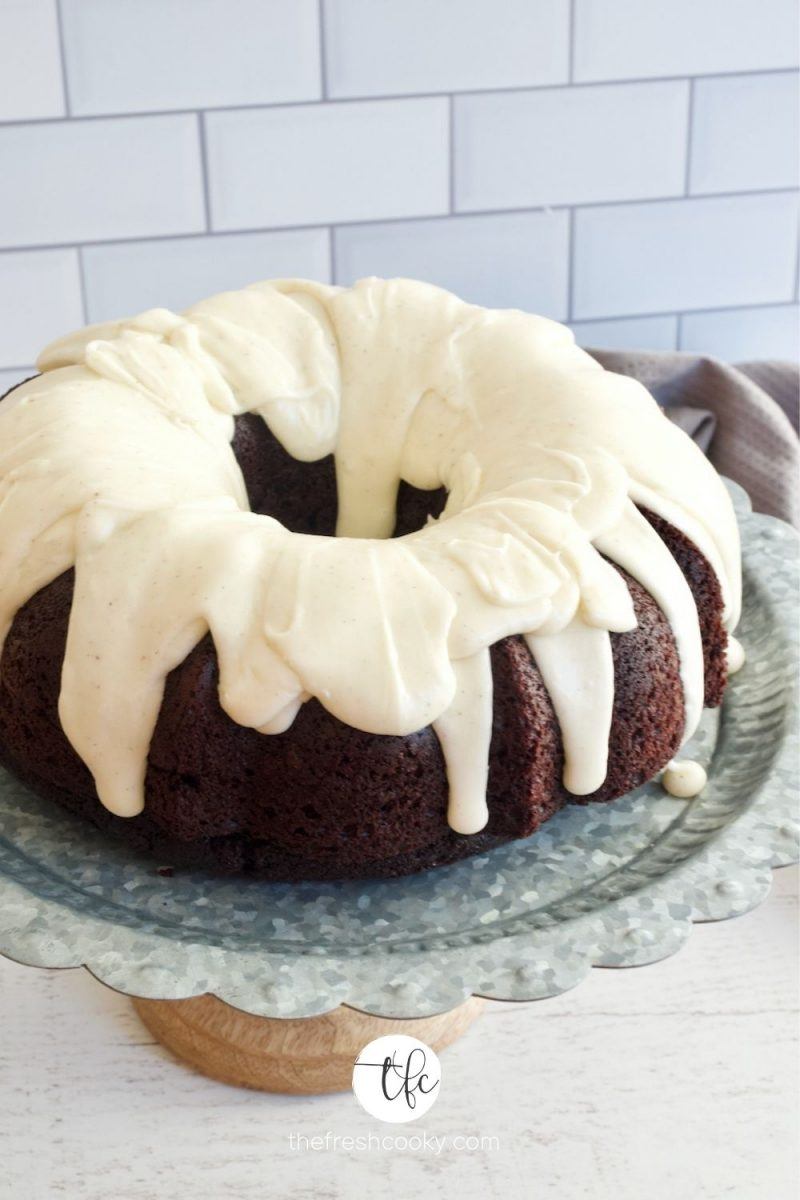 Image of chocolate cake topped with vanilla buttercream glaze, sitting on top of a galvanized cake stand