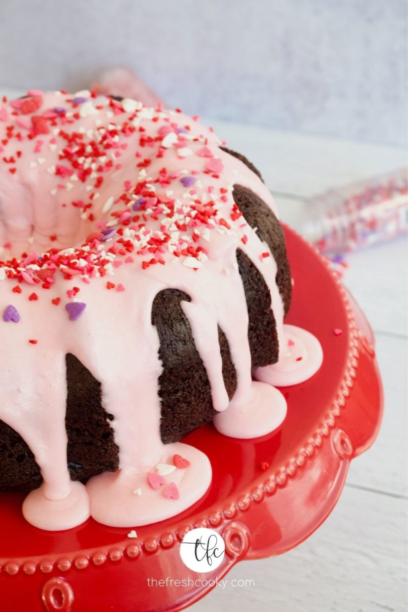 Pink buttercream glaze on top of a chocolate bundt cake with heart sprinkles on top