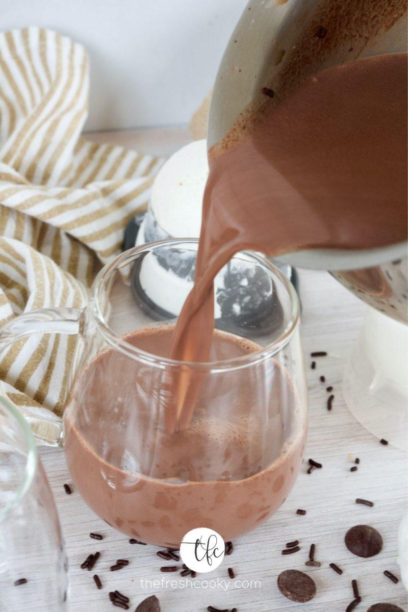 A small saucepan pouring homemade hot chocolate into a glass mug.