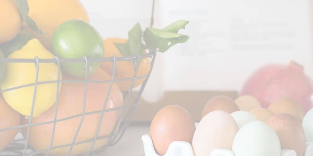 background faded image of basket of citrus and eggs