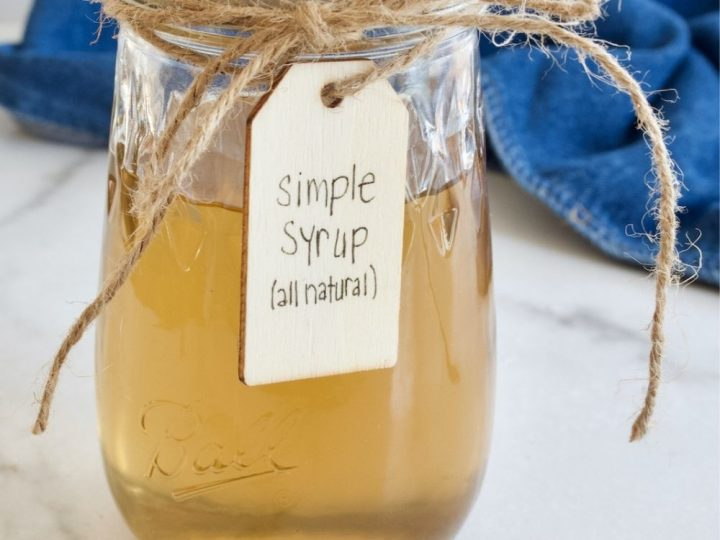 A mason jar filled with a golden amber cane sugar simple syrup, tied with twine and a label.