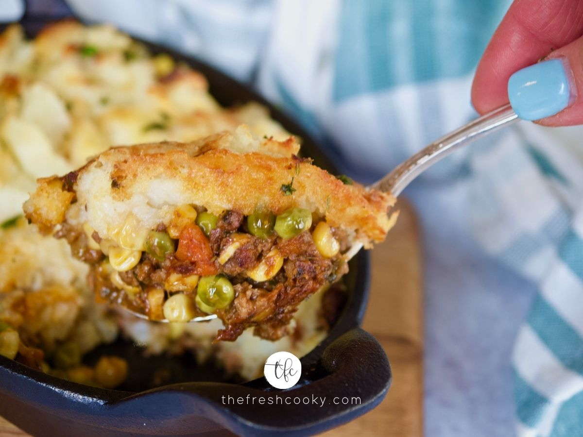 cast iron pan filled with skillet shepherd's pie with hands bringing up spoonful.