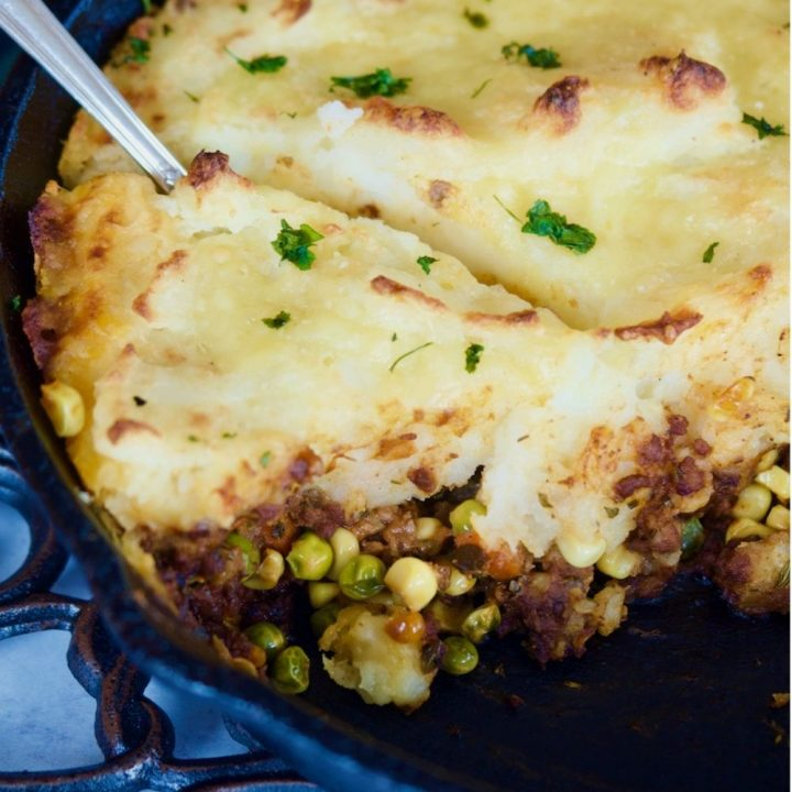 Shepherd's meat pie in a cast iron skillet with a spoon dug into the mashed potato topping.