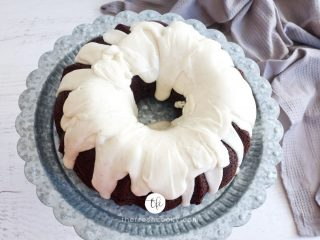 landscape image of chocolate bundt cake drizzled with vanilla buttercream glaze on pedestal with gray tea towel
