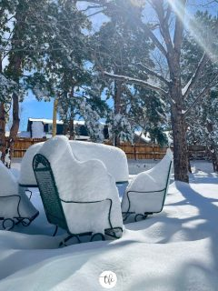Post monster snowstorm, outdoor table and chairs with 19 inches of snow on a bright sunny day.
