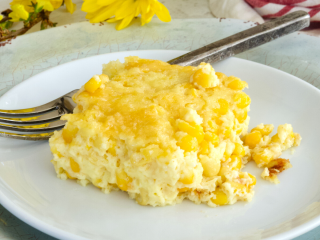 Square image for corn pudding casserole with square of corn pudding on a plate with a fork and yellow flowers behind.
