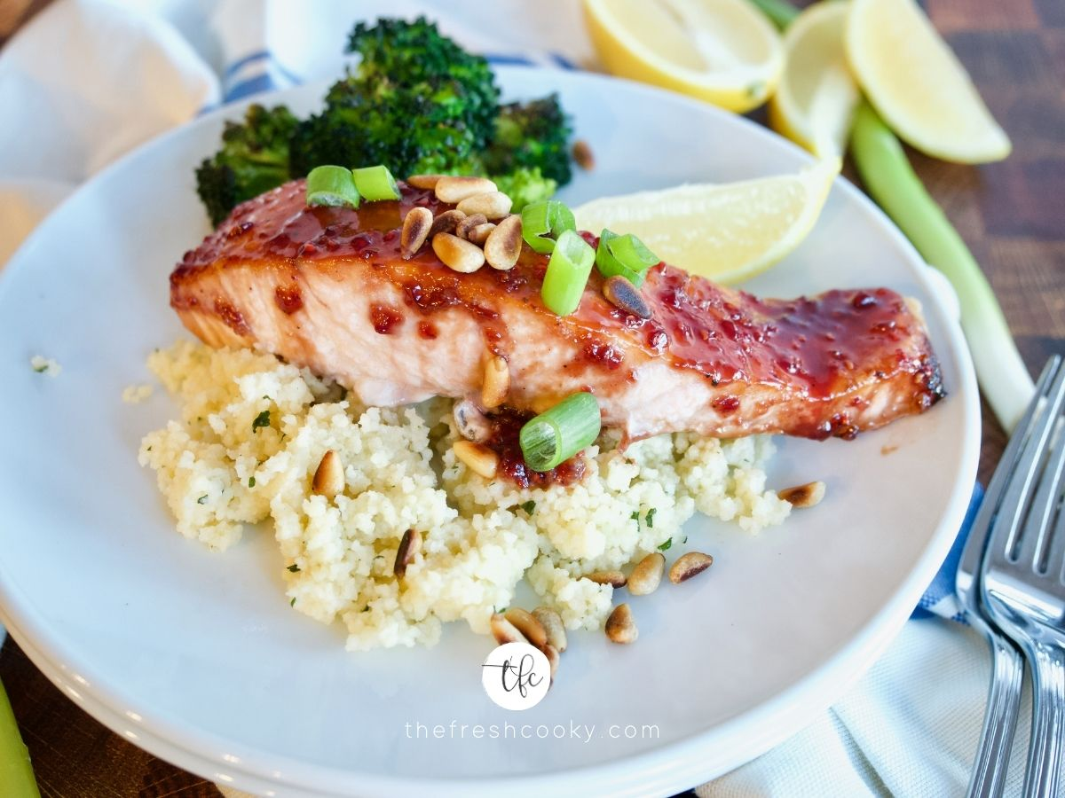 facebook image for raspberry glazed salmon plated on top of a bed of couscous with roasted broccoli.