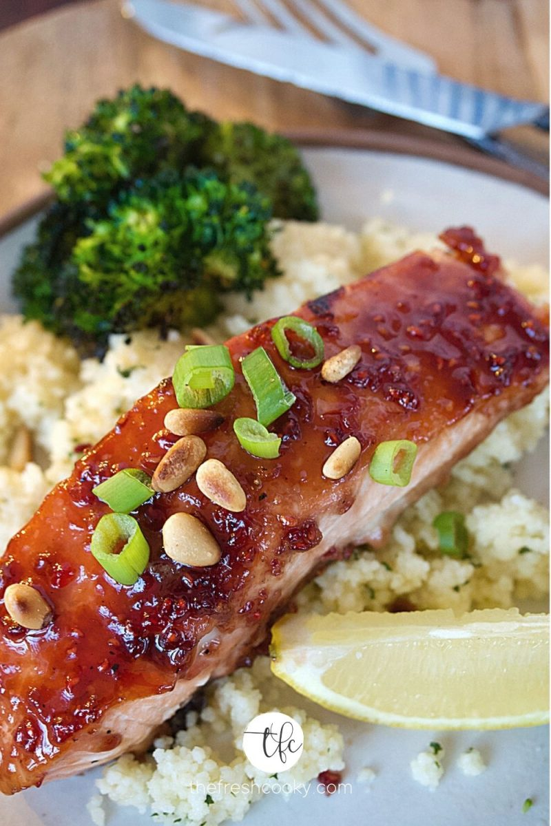 close up of raspberry glazed salmon on plate with couscous and roasted broccoli.