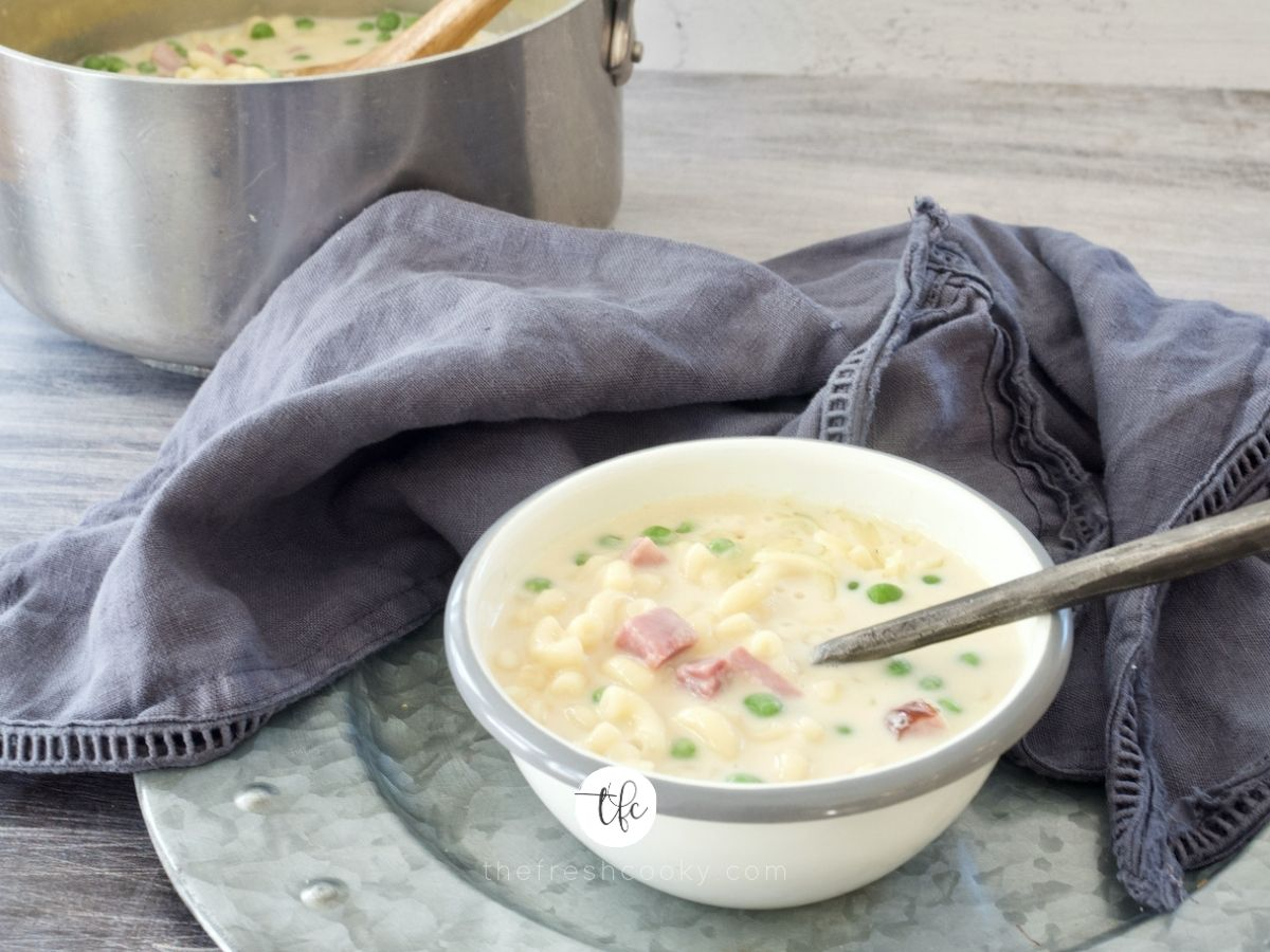 A delicious bowl of Ham, mac & cheese soup on a galvanized platter with soup pot behind.