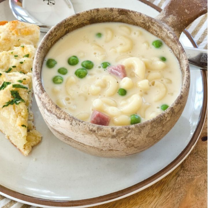 Stoneware bowl full of Ham, Mac & Cheese Soup with wedge of biscuit on wooden charger.