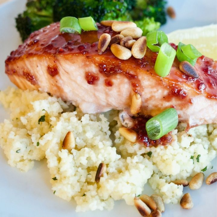 healthy raspberry glazed salmon on a bed of couscous with roasted broccoli in background.