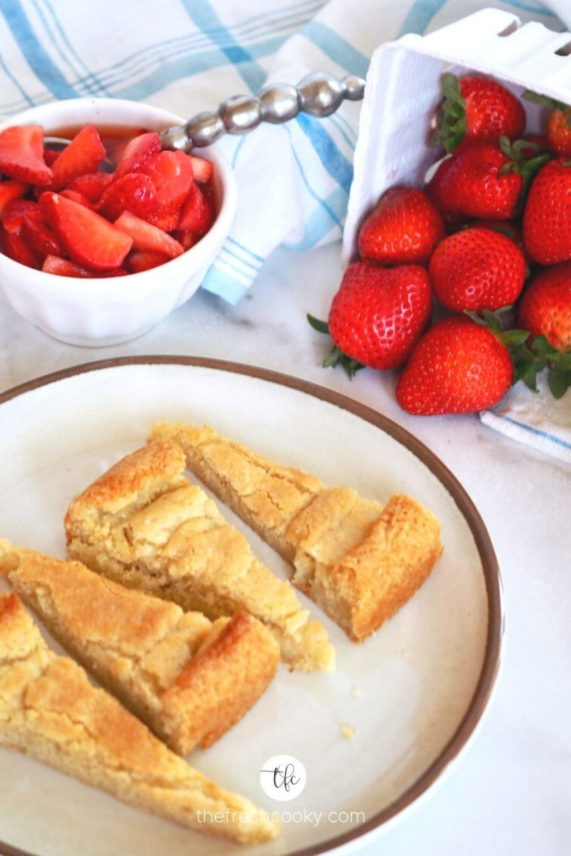 Old Fashioned Strawberry Shortcake wedges on plate with diced and whole strawberries in background.