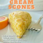 Pin for best orange scones with image of single scone on white plate with wedge of orange and a fork.