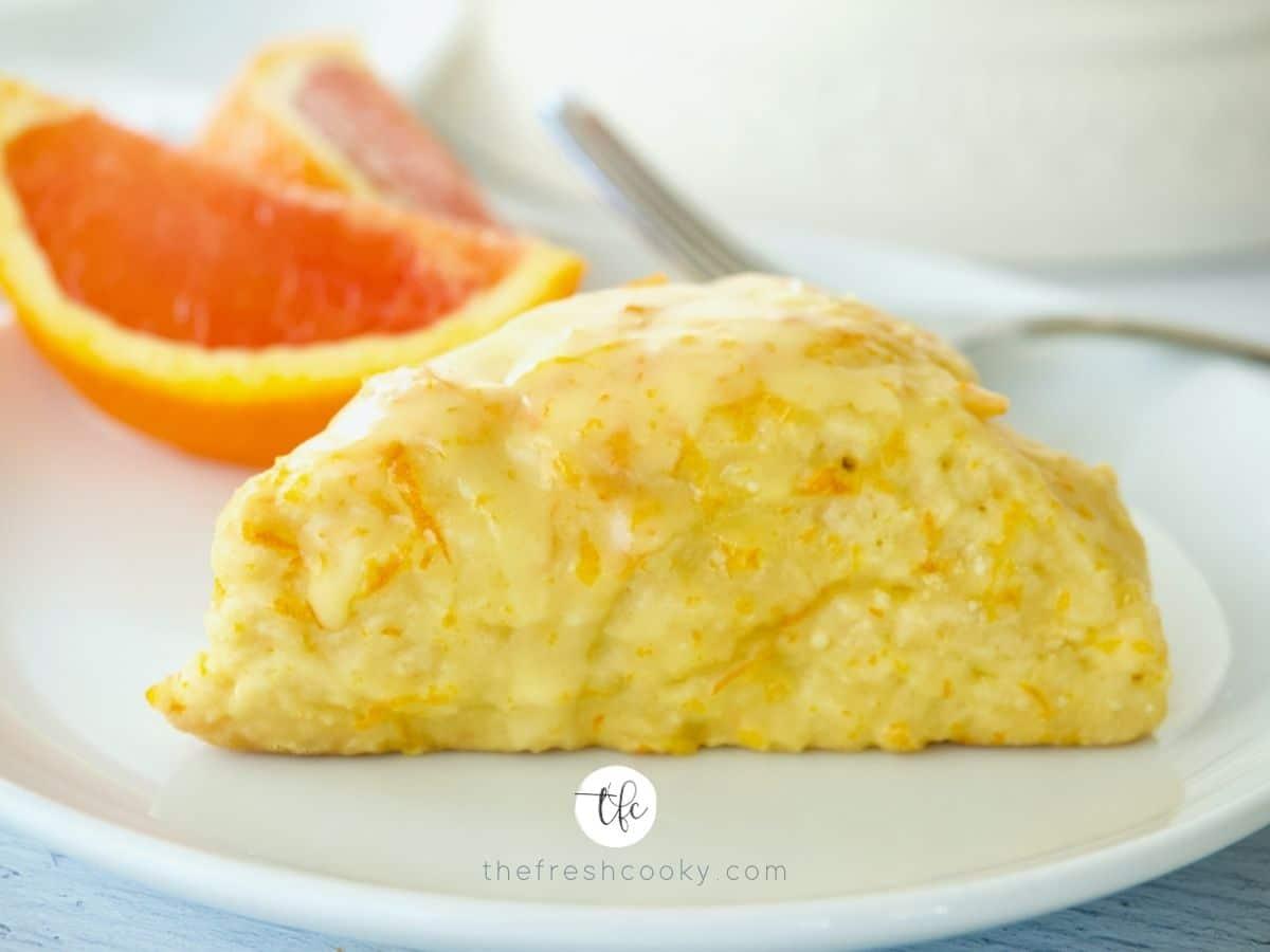 Single Orange Scone on a plate with slices of fresh orange behind.