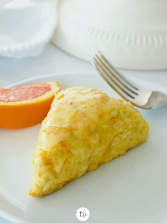 Image of orange scone on white plate with wedge of orange and fork.
