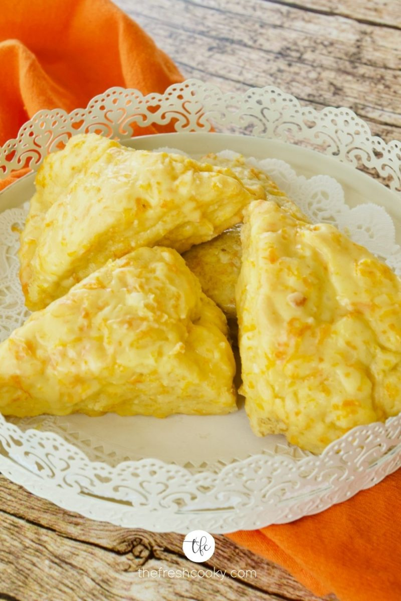 4 orange scones on a pretty decorative plate or platter with orange napkin behind.