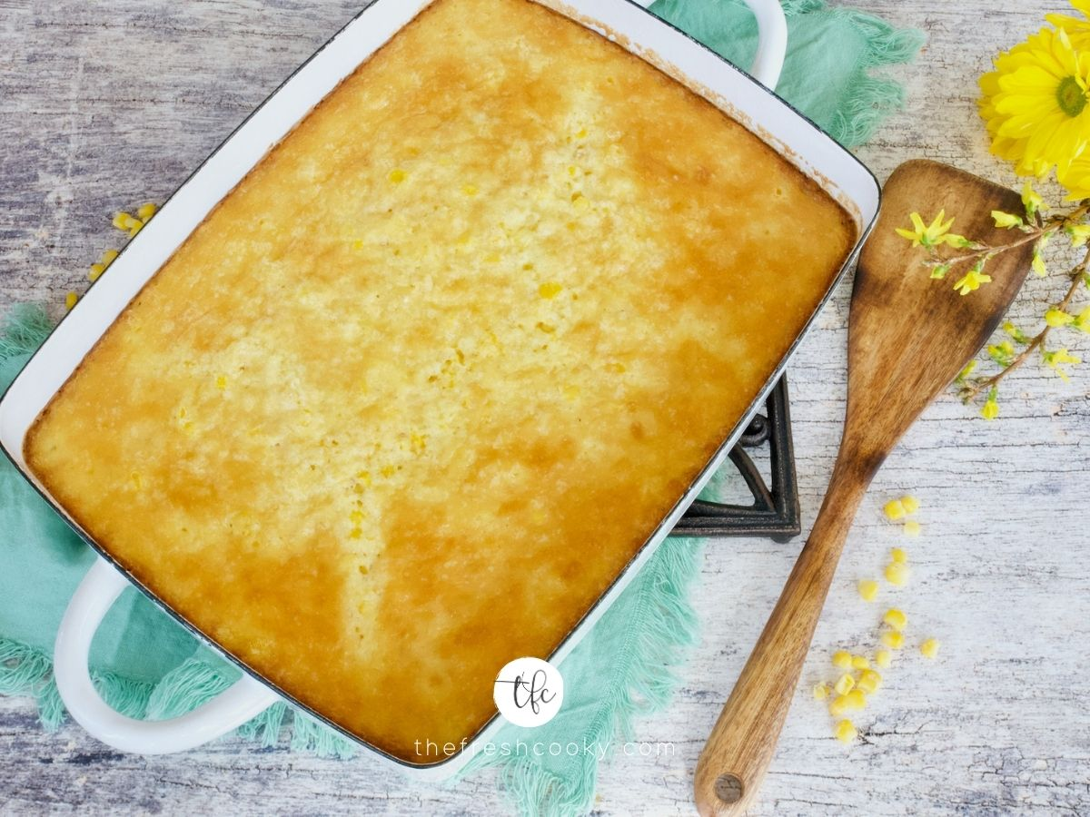 Baked corn pudding casserole in casserole with serving spatula.