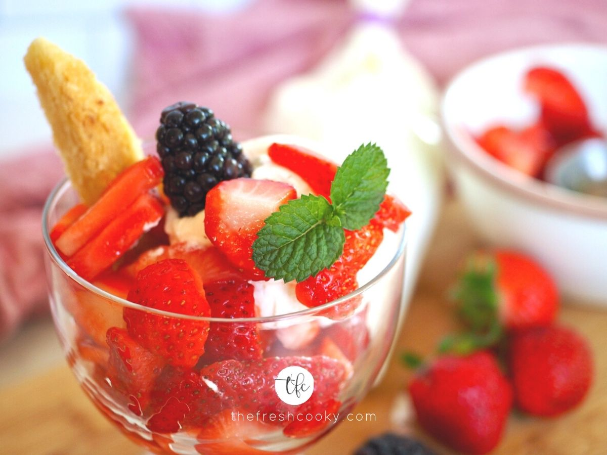 old-fashioned strawberry shortcake in glass dish with whipped cream and sprig of mint.