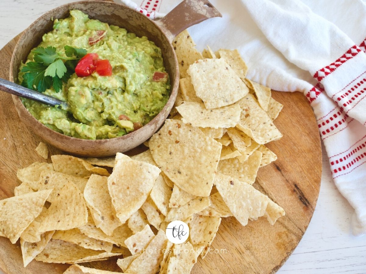 Facebook image for super simple guacamole on a wooden tray with tortilla chips and spoon in bowl of guacamole.