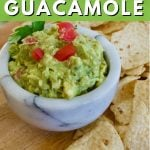 Pin for 5 minute authentic guacamole recipe with marble bowl filled with fresh, bright green guacamole and chips around it.