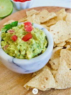 marble bowl filled with homemade guacamole on a wooden tray with tortilla chips.