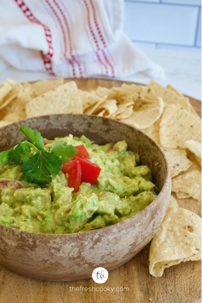 Fresh homemade simple guacamole in a wooden bowl on a tray with fresh tortilla chips.