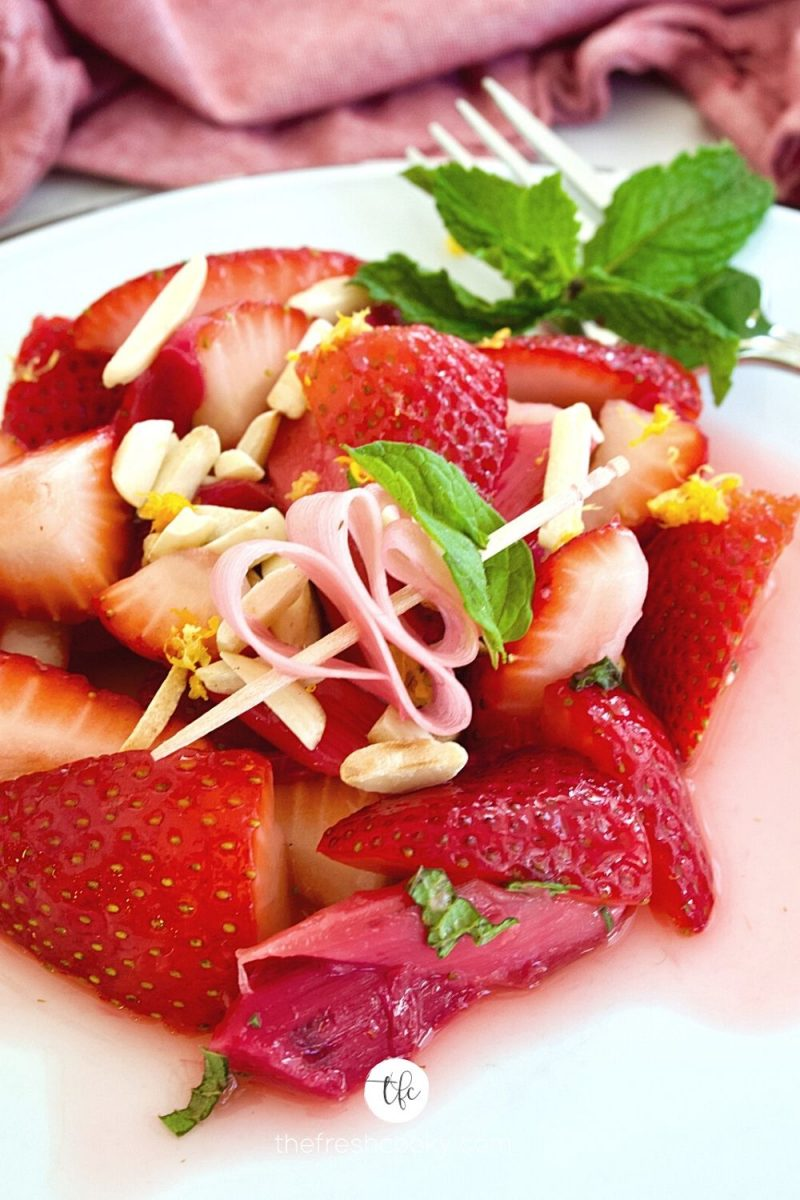 White plate with strawberry rhubarb salad with ribbon of rhubarb on pick with sprig of mint.