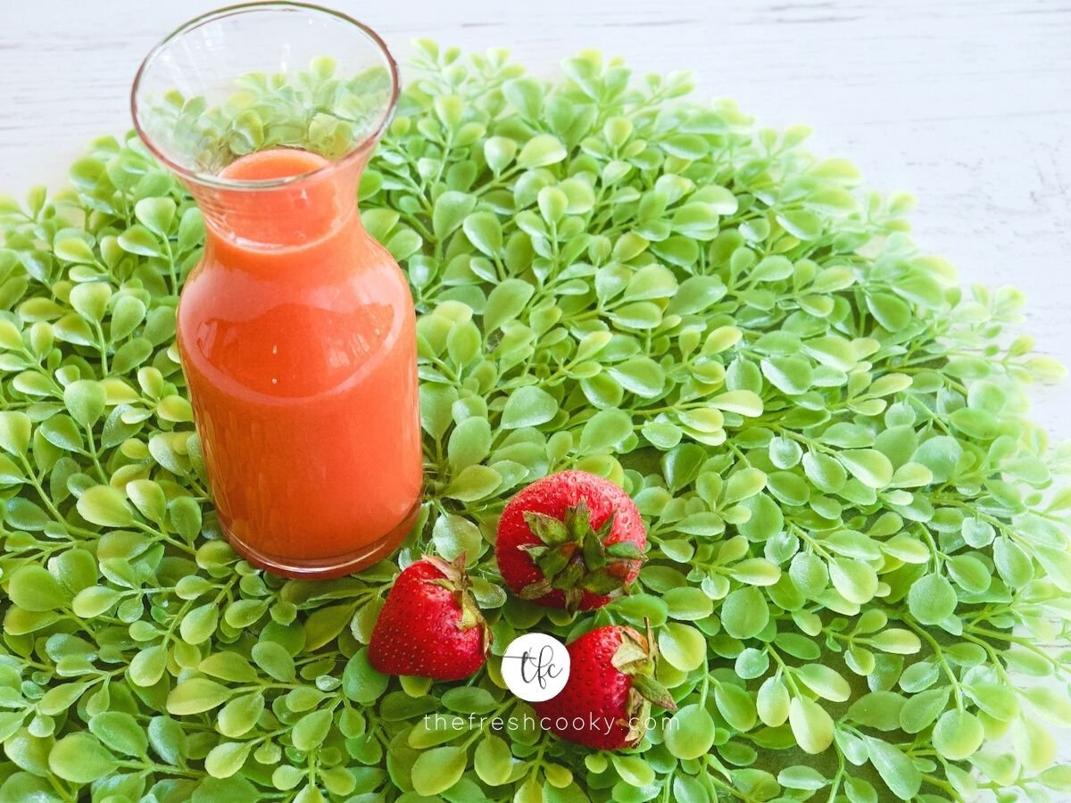 Fresh Strawberry Syrup in jar with three strawberries nearby, sitting on bed of greens.
