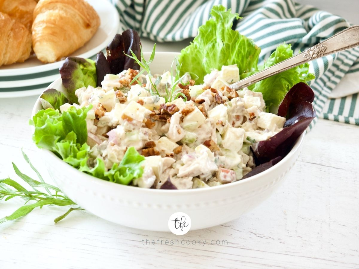 Tarragon Chicken Salad in large serving bowl with lettuce lining it and croissants in background.